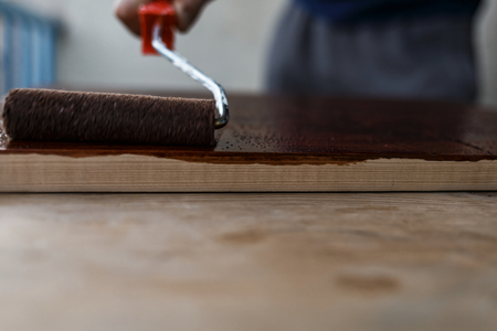 Man painting (dye) wooden plank with a roller Imagens - 104975369