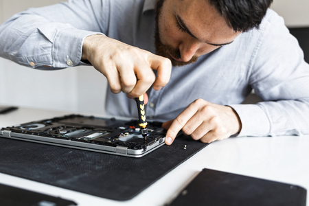 Computer repair technician working on a laptop with small tools Imagens - 104975363