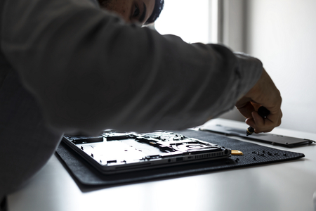 Computer repair technician working on a laptop with small tools