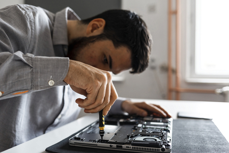 Computer repair technician working on a laptop with small tools Imagens - 104975388
