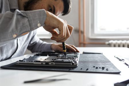 Computer repair technician working on a laptop with small tools Imagens - 104975378