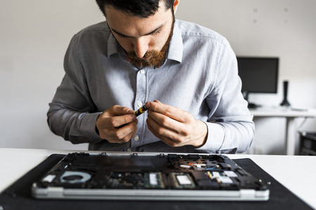 Computer repair technician working on a laptop with small tools Imagens - 104975381