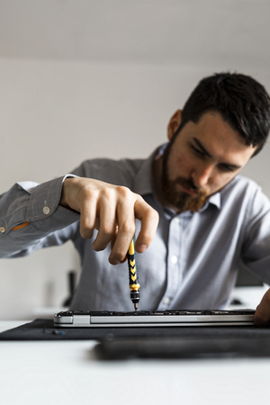 Computer repair technician working on a laptop with small tools Imagens - 104975382
