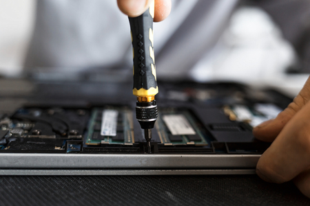 Computer repair technician working on a laptop with small tools Imagens - 104975384