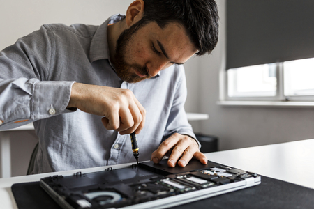 Close up of male hands fixing a laptop, using a screwdriver