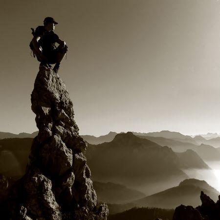 bergbeklimmen: Bergdecor - man op een rots boven Stockfoto