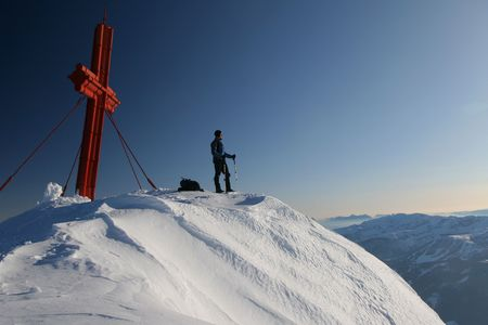 Alpinist at a summit cross Stock Photo - 2362869
