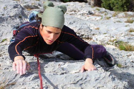 limestone: Rock climbing. Young woman climbing a limestone rock