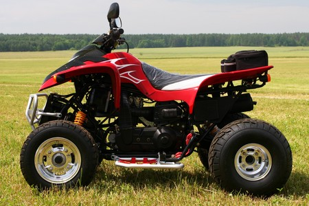 Red quad bike (ATV)  on green field.  photo