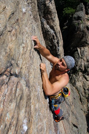 rockclimber: Male rock-climber  on a granite wall Stock Photo