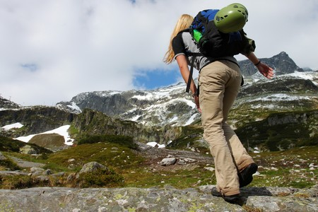 trekking pole: Young girl with backpack in the mountains
