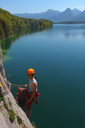 adrenaline: Young woman with climbing gear above alpine lake in Upper Austria Stock Photo