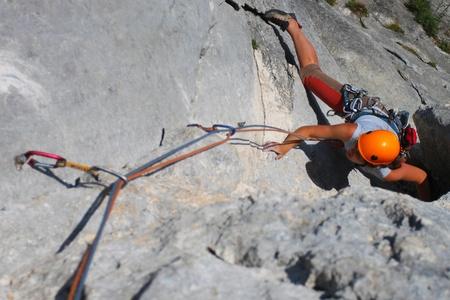 Rock climbing. Young woman climbing a limestone rock photo