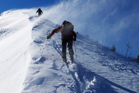 windstorm: Two climbers ascending snow ridge in snow storm Stock Photo