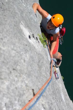 rock climbing: Summer climbing. Young woman climbing a limestone rock
