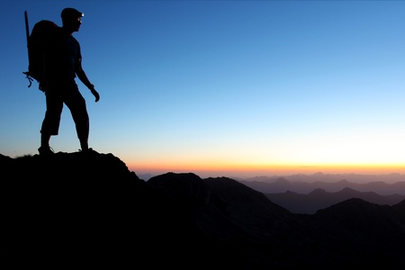 trekking: Silhouette of a man in the mountains at dawn