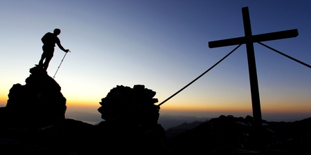 Silhouette of a man on a mountain summit at dawn photo