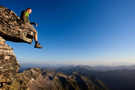 outdoor activities: Young man sitting on rock above mountain range