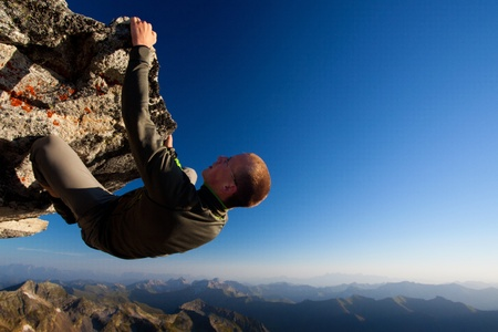 to climb: Young man climbing the rock high above mountain range Stock Photo
