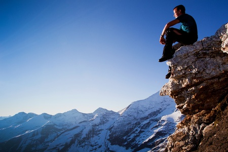 tauern: Young man sitting on rock above mountain range
