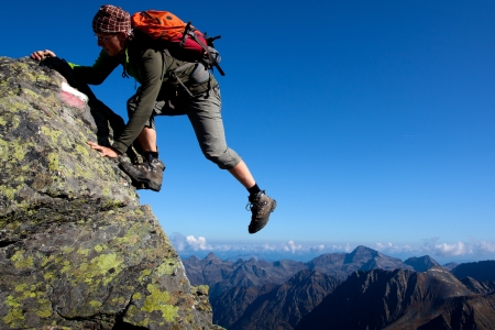 Young man climbing the mountain ridge photo