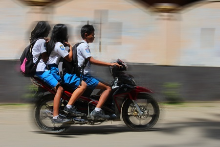RANTEPAO, INDONESIA - JULY 20: Three teenage students riding a motorcycle on Sulawesi July 20, 2011 in Rantepao, Indonesia