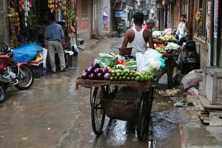 DELHI, INDIA - JULY 31: Man pulling a rickshaw full of vegetable in streets of Old Delhi July 31, 2008 in Delhi, India