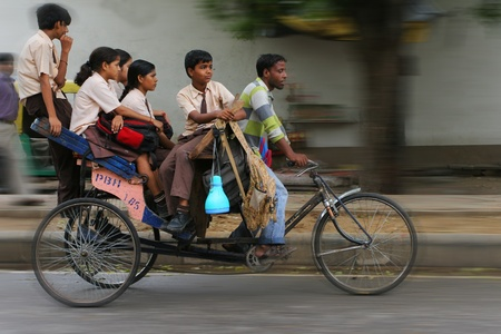 DELHI, INDIA - JULY 31: Big Indian family riding a cycle rickshaw in the streets of Delhi July 31, 2008 in Delhi, India Stock Photo - 10912064