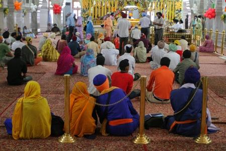 sikhism: DELHI, INDIA - SEPTEMBER 6: Colourful interior of Sikh temple full of people September 6, 2008 in Delhi, India