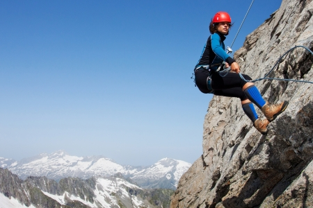 rock climbing: Young woman abseiling rock face in the Alps with large copy space