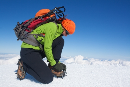 crampons: Young woman putting on her crampons Stock Photo