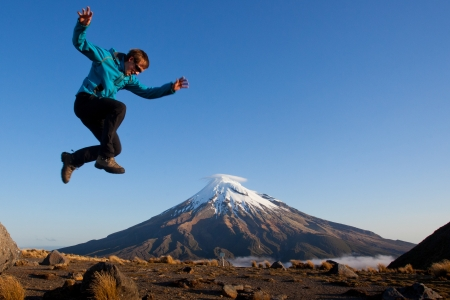 new zealand: Young man jumping above the volcano Stock Photo