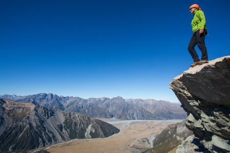 trekker: Young woman standing above mountain valley Stock Photo