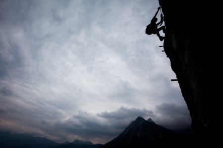 extreme danger: Silhouette of a climber above mountain peaks. Great copy space. Stock Photo