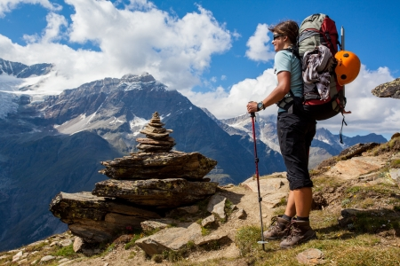 mountaineer: Young woman with backpack on a mountain trek