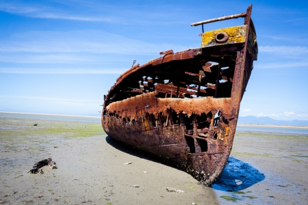 Rusty old shipwreck trapped on a beach.