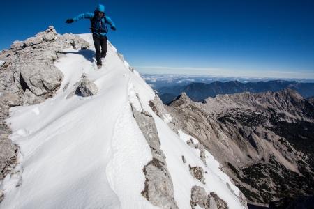Young man running along snowy mountain ridge
