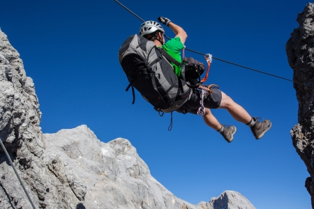 traverse: Young man going accross tyrolean traverse on via ferrata  Klettersteig  Stock Photo