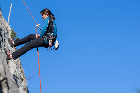 Young woman abseiling steep rock face