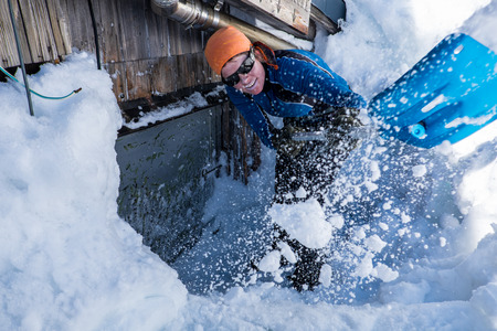 Young woman shoveling snow out of the doors photo