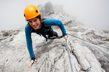 Young woman climbing steep rock wall