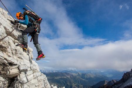 Młoda kobieta wspinaczka po stałym liny wysoko nad górskiej dolinie Zdjęcie Seryjne