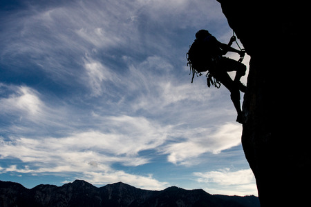 mountain: Silhouette of a climber on a verctical wall Stock Photo