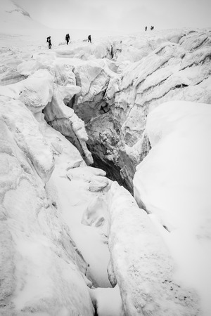crevasse: Group of climbers on a glacier with huge crevasse