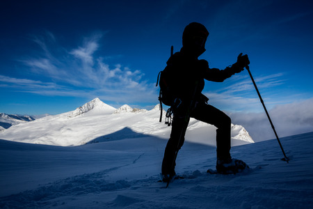 ascend: Silhouette of a man doing a snowshoe mountain ascend