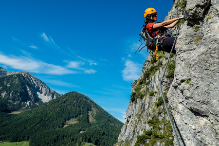 Young woman in helmet climbing via ferrata in  Austrian Alps Stockfoto
