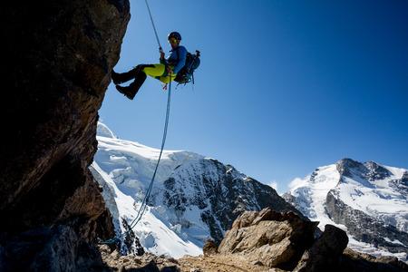 trepadoras: Mujer joven rappel roca escarpada en la montaña