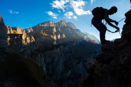 extreme sports: Silhoutte of a man climbing in the mountains