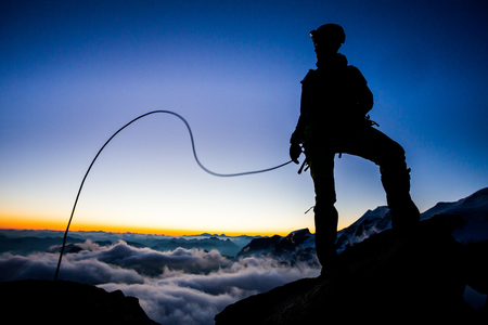 ascent: Silhouette of a mountaineer during morning ascent Stock Photo
