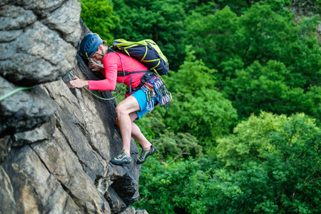 climb: Young woman struggling to climb a rock